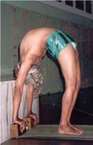 Postura en retroflexión con ayuda de tacos del maestro Iyengar